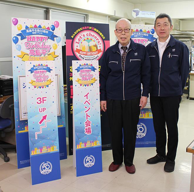 制作物の前で狩野会長(左)と増田部長