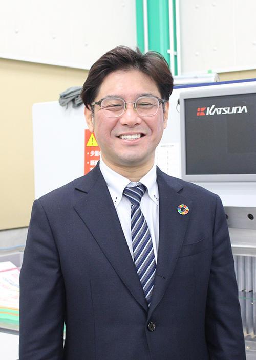 勝田断裁機の前で恵利社長